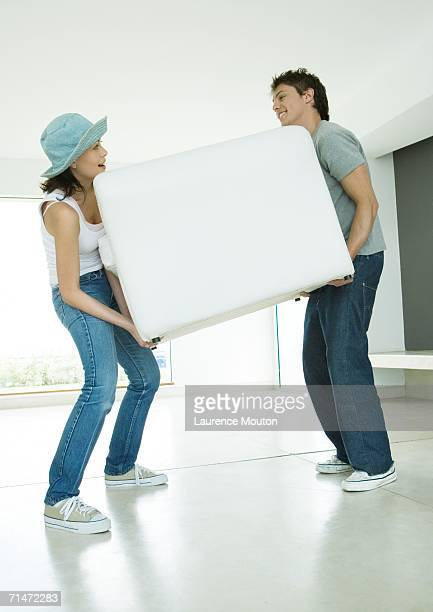 Couple moving armchair together