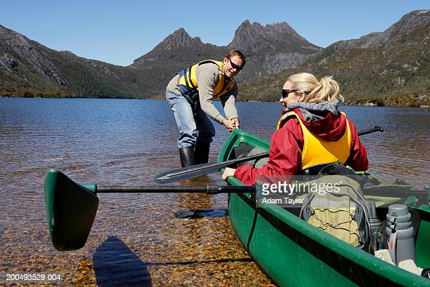 Couple moving canoe into water