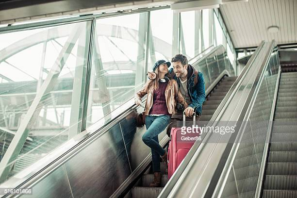 Couple moving down escalator
