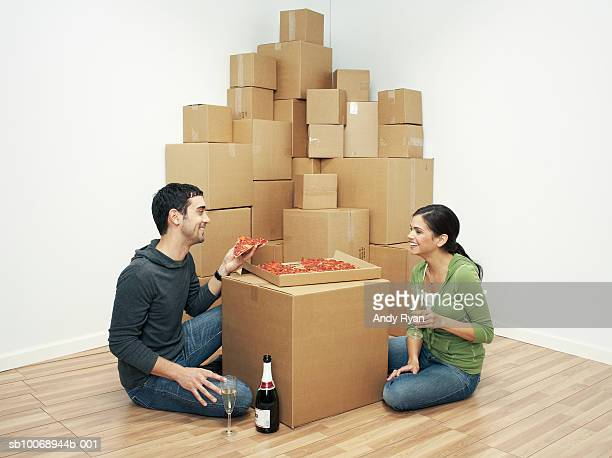 Couple moving house and eating pizza on cardboard box