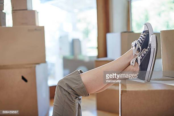 Couple moving house, womans feet on a box