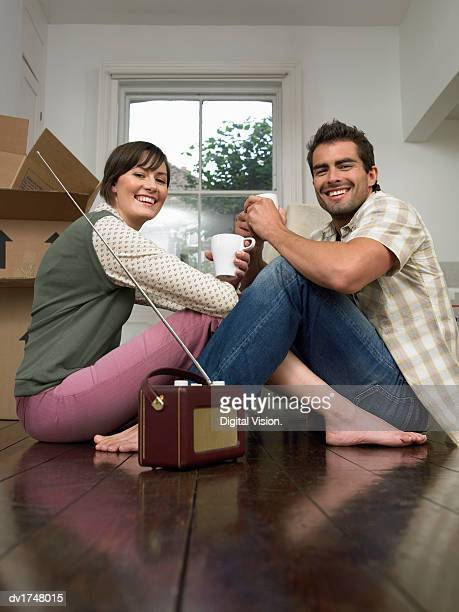 Couple Moving into a House, Sitting on a Wooden Floor With a Radio Holding Mugs