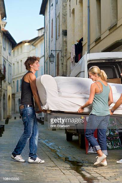 Couple moving sofa in street