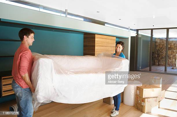 Couple moving sofa into new home