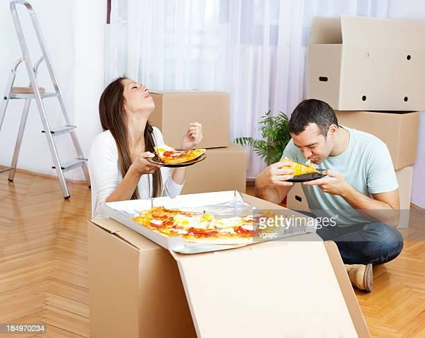 Couple se déplacer à nouvelle maison manger pizza