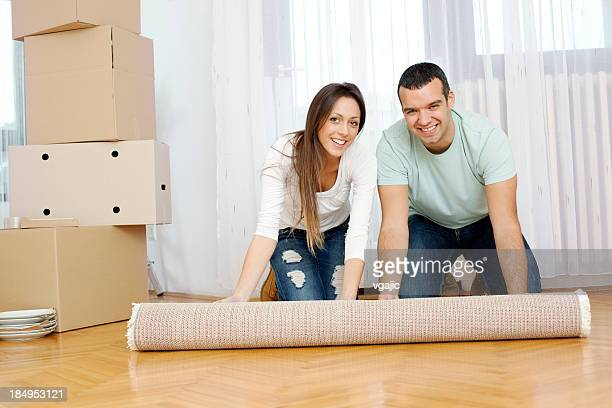 Couple Moving to new house - unrolling carpet