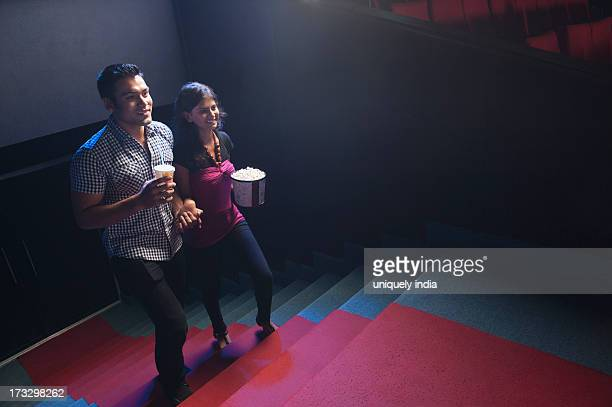 Couple moving up on steps in a cinema hall