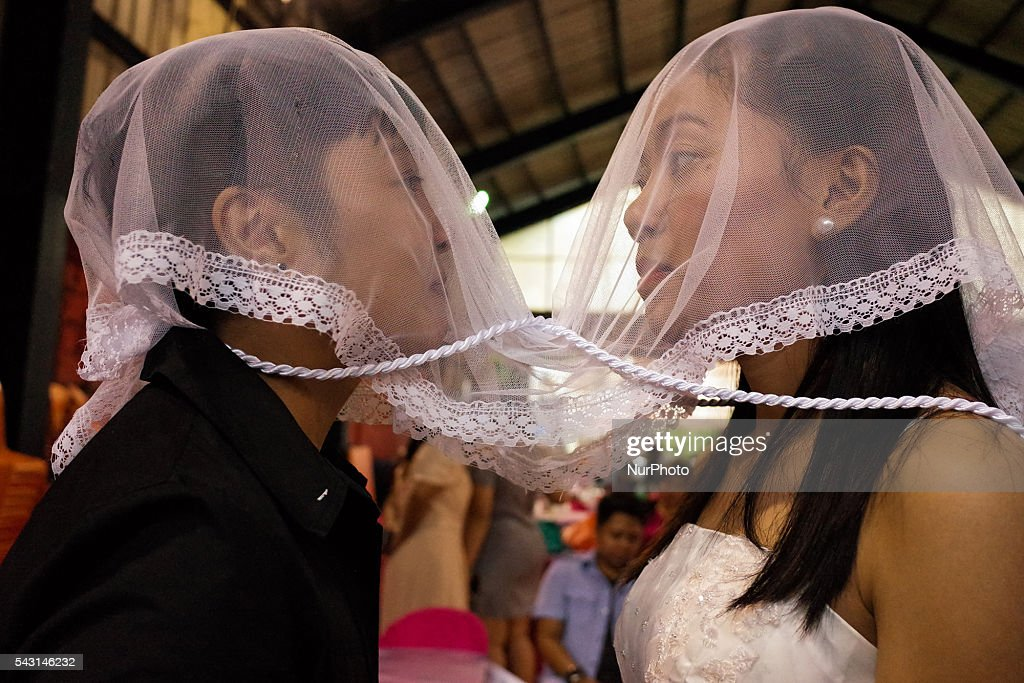 "LGBT couple Nabel Ambayol and Mary Grace Timkang exchange vows during a mass wedding ceremony at Barangay Sangandaan in Quezon City on Sunday, 26 June 2016. The LGBT Christian Church, a small Christian ecumenical group, performed its own ""wedding rites"" for eight couples at a basketball court on Sunday, although same-sex unions are not legally recognized and rejected by the dominant Roman Catholic church in the country."