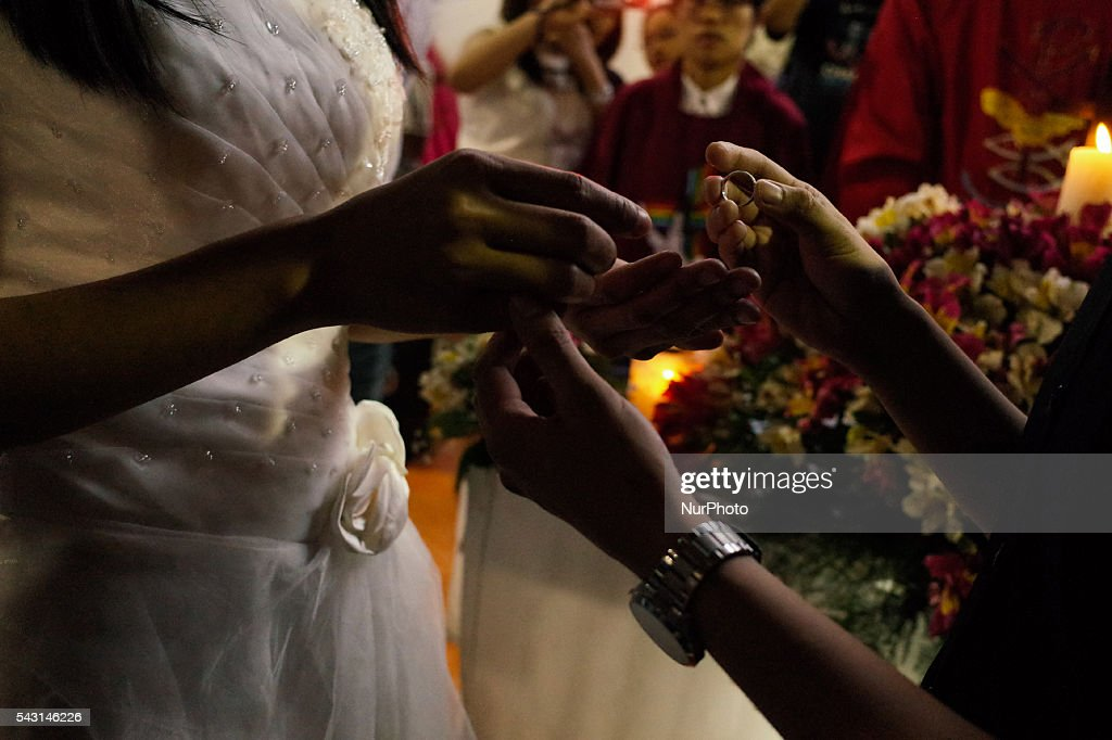 "LGBT couple Nabel Ambayol and Mary Grace Timkang exchange wedding rings during a mass wedding ceremony at Barangay Sangandaan in Quezon City on Sunday, 26 June 2016. The LGBT Christian Church, a small Christian ecumenical group, performed its own ""wedding rites"" for eight couples at a basketball court on Sunday, although same-sex unions are not legally recognized and rejected by the dominant Roman Catholic church in the country."