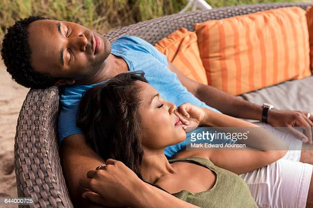 Couple napping on lawn furniture