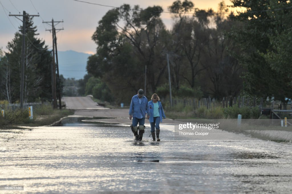 A couple navigate a submerged road September 17, 2013 near Evans, Colorado. Even as flooding subsides, many in the hardest hit areas of the state remain stranded by washed out roads and rushing creeks and without water and power.
