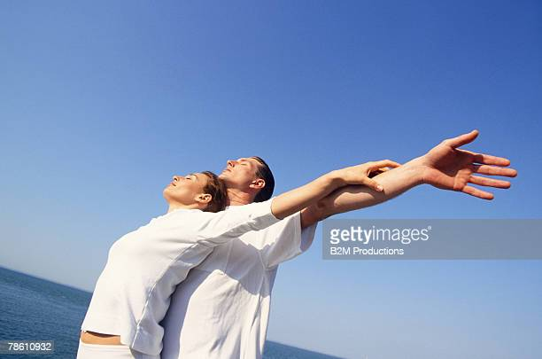 Couple near ocean with arms outstretched