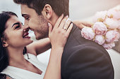 Just married! Portrait of beautiful young romantic couple is hugging and enjoying being together. Attractive woman in wedding dress with bridal bouquet in hands and handsome man in suit are celebratin