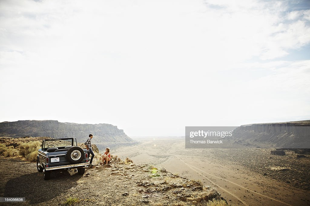 Couple next to convertible on side of desert road