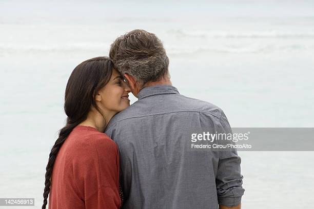 Couple nuzzling at the beach, rear view