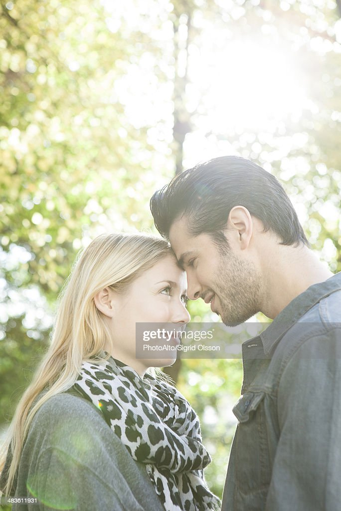 Couple nuzzling each other outdoors : Stock Photo