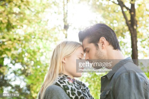 Couple nuzzling with eyes closed outdoors