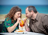 Couple of adults take an appetizer at the bar in Pane e Pomodoro's Beach in Bari (Apulia)