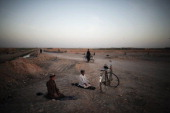 A couple of Afghan boys stops to ride on a bicycle to pray at down as US Marine of the 3rd Battalion 6th Marines patrol nearby in Marjah Helmand...