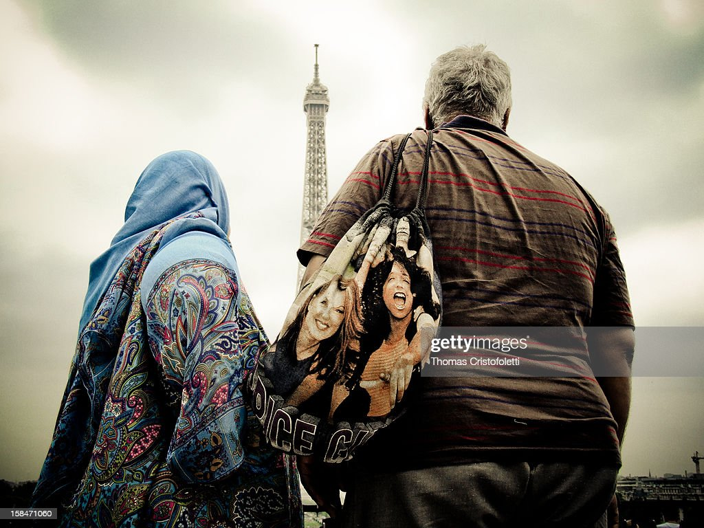 A couple of arab tourist staring at the Eiffel Tower, in Paris (France).