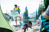 Young couple hiking together in stunning mountain wilderness near the lake. POV from the tent. Woman sitting inside, man with backpack and looking for trails on the map