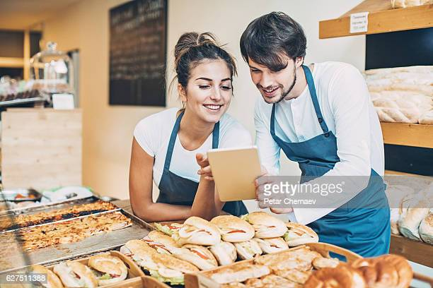 Couple of bakers with digital tablet