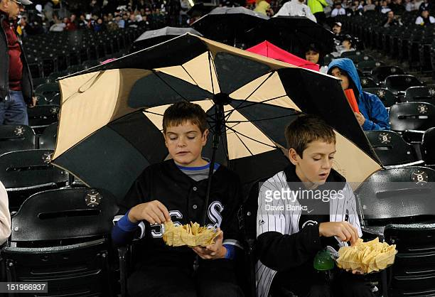 A couple of baseball fans try to stay dry as the game between the Chicago White Sox and the Detroit Tigers has been cacelled on September 13 2012 at...