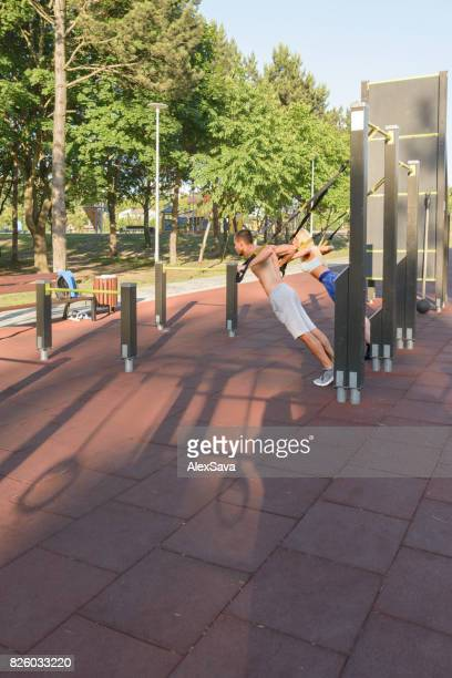 Couple of bodybuilders doing calisthenics exercises outdoor in the park