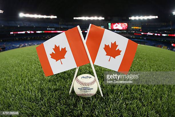 A couple of Canadian flags next to a ball on the field on Canada Day before the start of the Toronto Blue Jays MLB game against the Boston Red Sox on...
