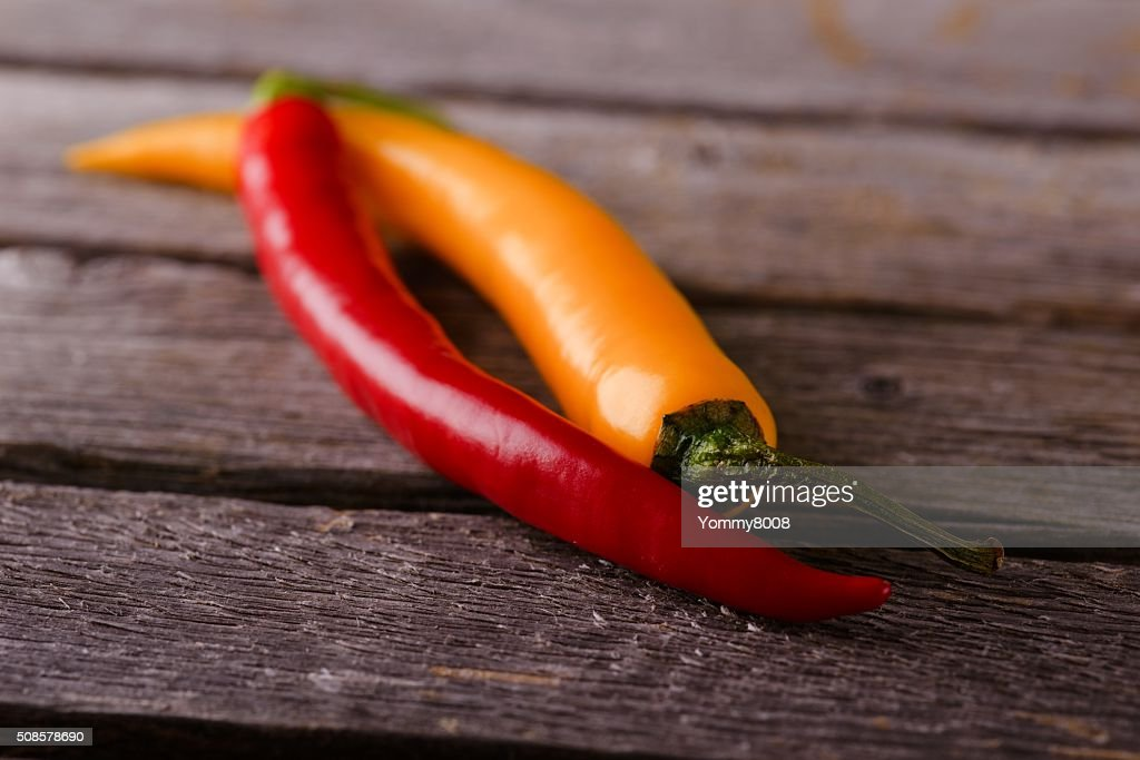 Couple of chili peppers on grey wooden board : Stock Photo