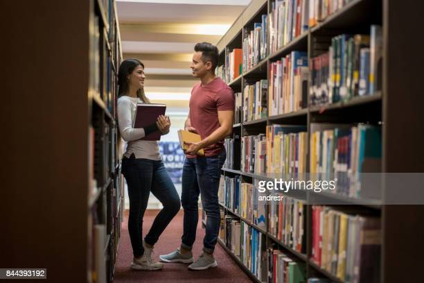 Couple of college students talking at the library