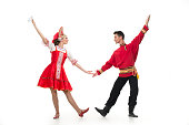 Couple of dancers in russian traditional costumes, girl in red sarafan and kokoshnik, boy in black trousers and red shirt . Studio shot isolated on white.