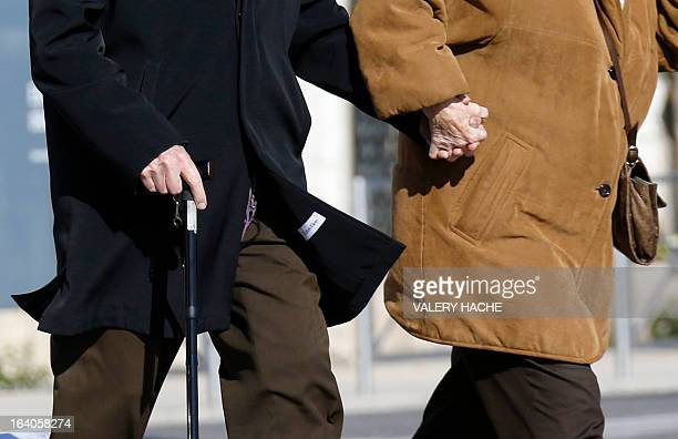 A couple of elderly people walk in Nice French Riviera on March 19 2013 AFP PHOTO / VALERY HACHE