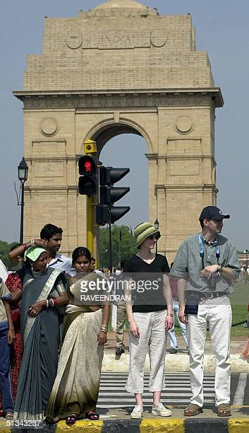 A couple of European tourists along with sariclad Indian women wait to cross a road at an intersection near the India Gate a popular tourist...