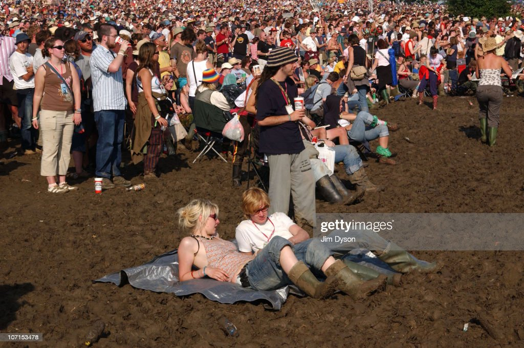 A couple of festival-goers lie in the mud, after a night of heavy rain during the Glastonbury Music Festival held at Worthy Farm on June 24, 2005 in Glastonbury, England.