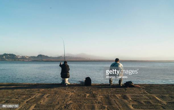 Couple of fisherman sitting down fishing in the Douro River