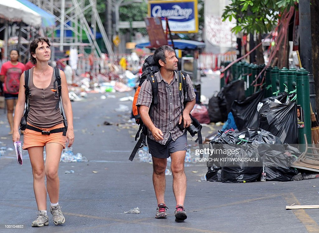 A couple of foreign tourist walks past anti-government's main protest area in Bangkok on May 21, 2010. Thailand picked up the pieces after violence and mayhem triggered by a crackdown on anti-government protests, as the focus swung to recovery and reconciliation in a divided nation.