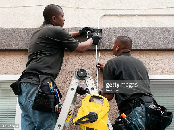 A couple of guys installing an electrical conduit