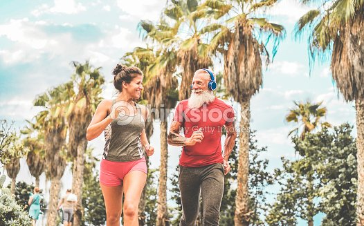 Couple Of Happy Fitness Friends Running Outdoor Joggers