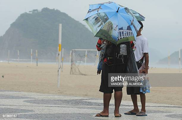 A couple of hawkers crying their umbrellas await for customers March 2 2010 in Copacabana Beach Rio de Janeiro Brazil After a wave of heat Rio is...