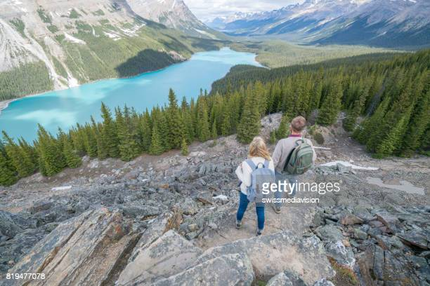Couple of hikers overlooking mountain lake