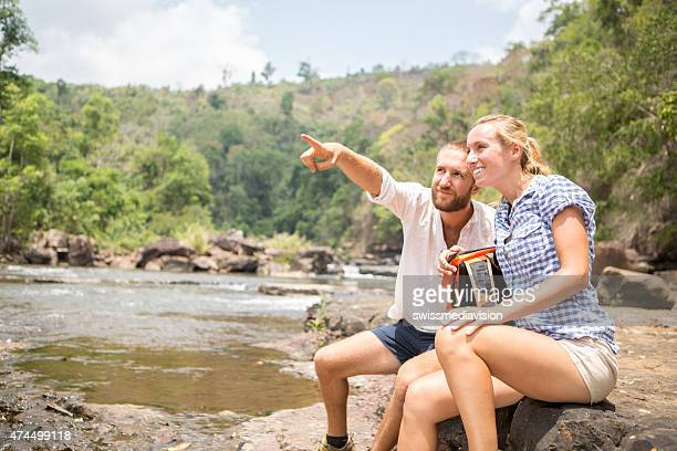 Couple of hikers relaxing, man showing direction