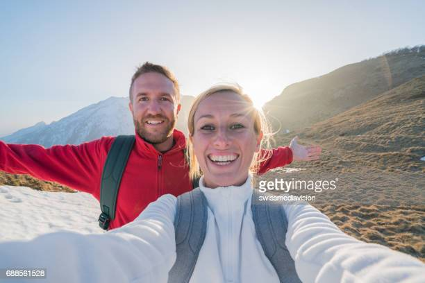 Couple of hikers taking selfie portrait on mountain trail