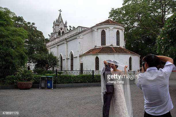 A couple of lover is taking wedding photos in front of a historical Catholic Cathedral Kulangsu is an island off the coast of Amoy city After the...