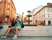 Tourists making selfie photo on motion action camera in old center of Ljubljana, Slovenia. Happy Couple sitting on a city embankment of the river on the background of square with fountain at sunset.