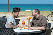 Couple of men take an appetizer at the bar in Pane e Pomodoro's Beach in Bari (Apulia)