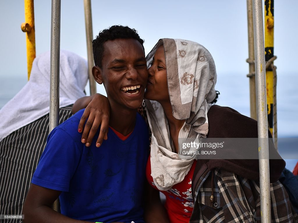 A couple of migrants jokes aboard the rescue ship 'Aquarius', on May 25, 2016 a day after a rescue operation off the Libyan coast. The Aquarius is a former North Atlantic fisheries protection ship now used by humanitarians SOS Mediterranee and Medecins Sans Frontieres (Doctors without Borders) which patrols to rescue migrants and refugees trying to reach Europe crossing the Mediterranean sea aboard rubber boats or old fishing boat. / AFP / GABRIEL