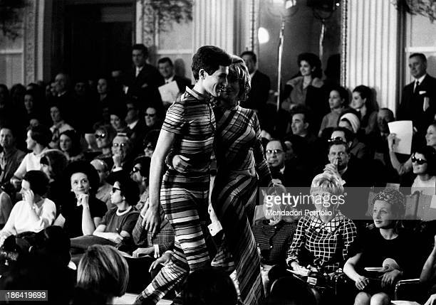 A couple of models is walking down on the catwalk in Palazzo Pitti on the occasion of the men and women knitwear springsummer collection 1967 fashion...
