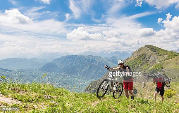Couple of mountainbikers at the rim, Italy