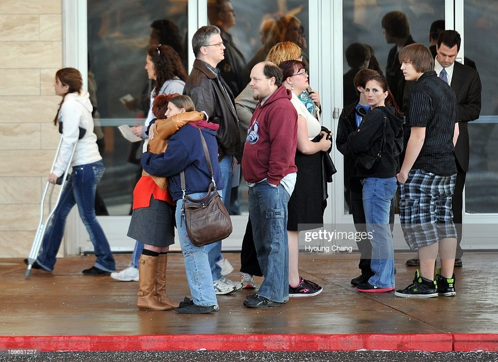 A couple of people comfort each other in front of the main entrance of the Century Aurora. The movie theater where a gunman killed 12 people and wounded dozens of others reopened with a private ceremony for victims, first responders and officials.